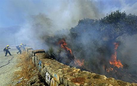 Firefighters battle a wildfire along Cajon Boulevard in the Cajon Pass north of Devore, Calif., Tuesday, Aug. 16, 2016. The fire erupted before noon and authorities said it had swelled to over 2,000 acres by early afternoon. Evacuations have been...