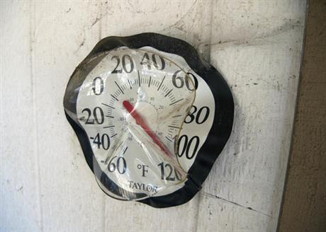 A partially melted thermometer is seen on a house that survived after a fire tore through Lower Lake, Calif., Tuesday, Aug. 16, 2016. A California man was arrested Monday on arson charges for allegedly sparking a wildfire that exploded over the...