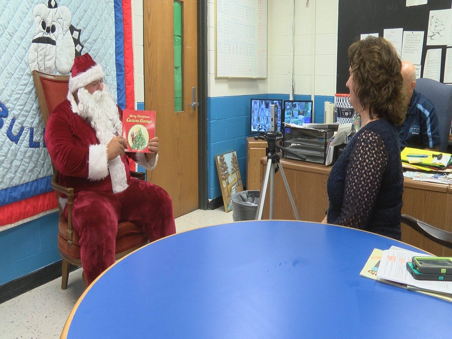 Hampton elementary math teacher Jake Jenkins dressed up as Santa Claus reads a Christmas story about Curious George.